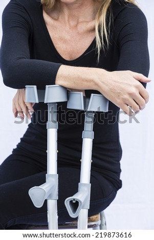 Woman and Crutches/ An injured woman using crutches - stock photo