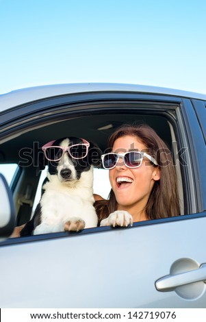 Woman and dog driving car on summer travel and having fun. Speed and vacation with pet funny concept. - stock photo