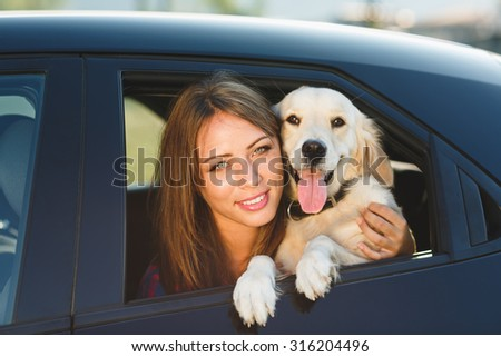 Woman and dog in car on summer travel. Vacation with pet concept. - stock photo