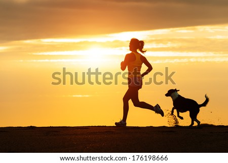 Woman and dog running free on beach on golden sunset. Fitness girl and her pet working out together. - stock photo