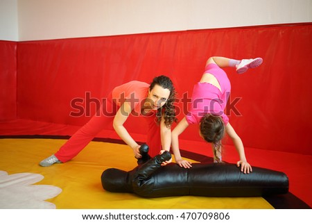 Woman and girl do fighting exercises with leather mannequin in gym with red wall