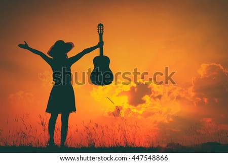 Woman and guitar with sunset silhouette.Summer Vacation concept.Vintage Tone. - stock photo