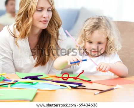 Woman and  her daughter cutting paper at home - stock photo