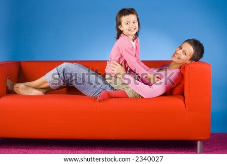 woman and her daughter on the red sofa - stock photo