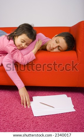 woman and her daughter sleeping on the red sofa - papers on the floor - stock photo
