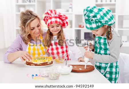 Woman and her daughters in the kitchen making a cake together - stock photo