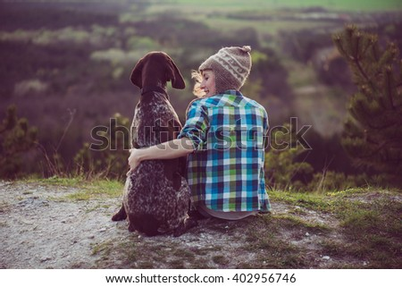 Woman and her dog posing outdoor. Girl loving and hugging tightly her dog and watching landscape. - stock photo