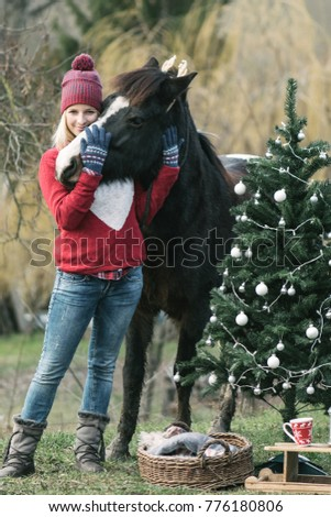 Woman and her horse outdoor. Christmas mood. Happy woman enjoy Christmas magic in garden.
