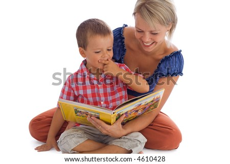 Woman and her little boy having fun reading a fairy tale - isolated on white with a bit of shadow - stock photo