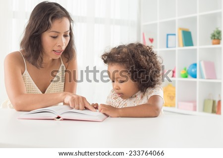 Woman and her little daughter reading together