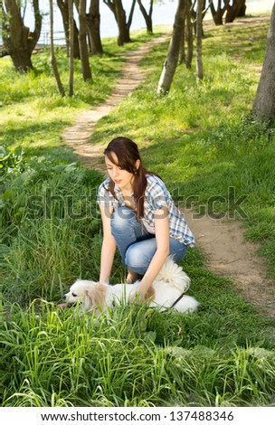 Woman and her small little toy breed dog out walking along a rural track through woodland in the summer sunshine - stock photo