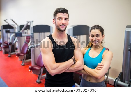 Woman and her trainer by the weights machines at the gym