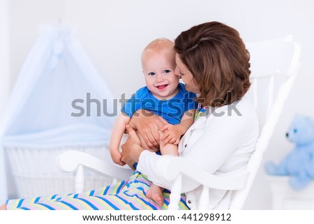 Woman and her young son in white bedroom with rocking chair and blue crib.  - stock photo