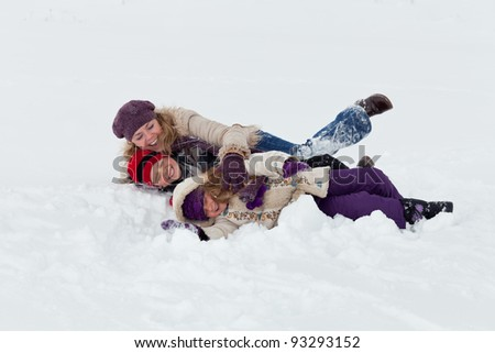 Woman and kids having fun in the snow - stock photo