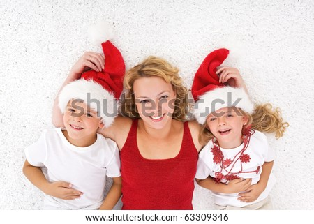 Woman and kids laying on the floor at christmas time wearing santa hats - stock photo
