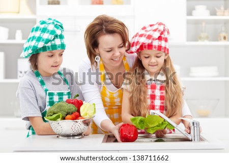 Woman and kids preparing the vegetables for a meal - washing them - stock photo