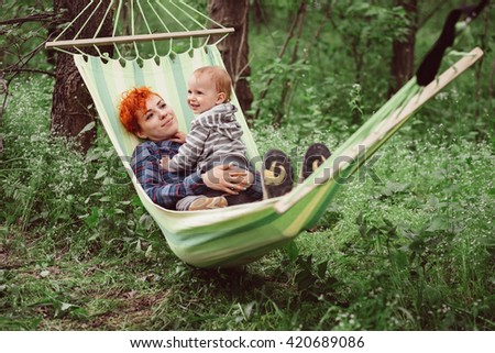 Woman and little baby boy relaxing in hammock. Mother and son swinging and resting in hammock in pleasant laziness of a summer outdoor weekend. Family outdoor, adventures and nature vacation.  - stock photo