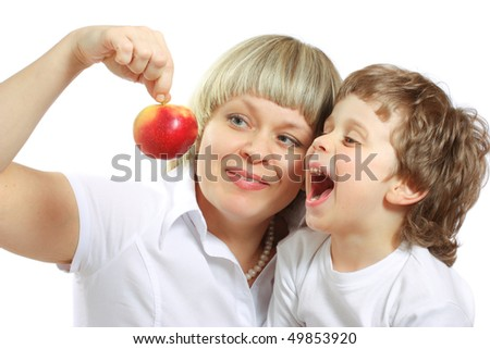 woman and little boy playing and eating an apple - stock photo