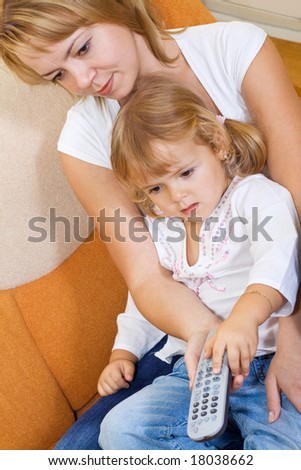 Woman and little girl changing channels on remote control