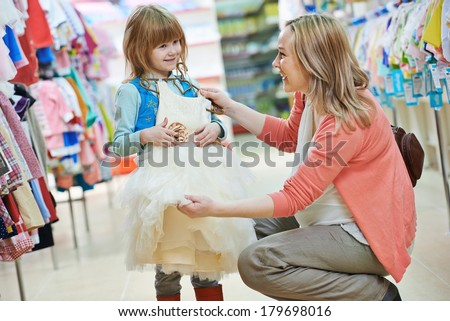 woman and little girl choosing and trying on dress clothes during shopping at garment supermarket - stock photo