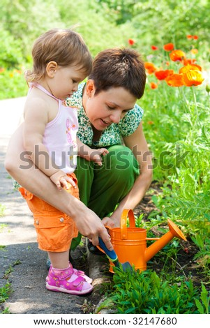 Woman and little girl doing gardening - stock photo