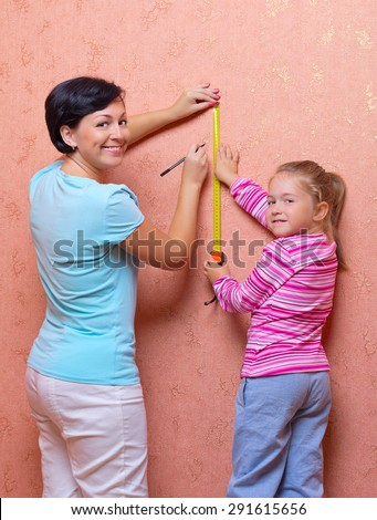Woman and little girl doing home repair - stock photo