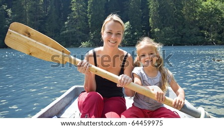 Woman and little girl in a small boat holding the  paddle - stock photo