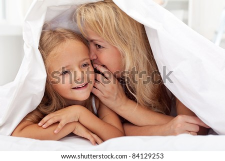 Woman and little girl sharing a secret whispering under the quilt - stock photo