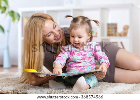 Woman and little girl watching a baby booklet - stock photo