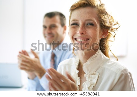 Woman and man applauding in business meeting - stock photo