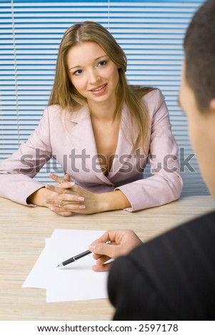 Woman and man at the office desk. Man's writting something - only his hands visable. Woman's talking or smiling. - stock photo