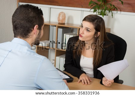 Woman and man at the office desk. Woman explains something - only his back visable.