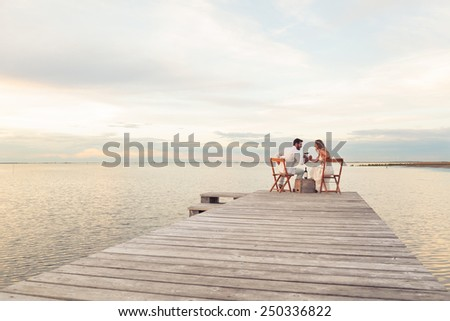 Woman and man couple drinking red wine at the seaside on a jetty - stock photo