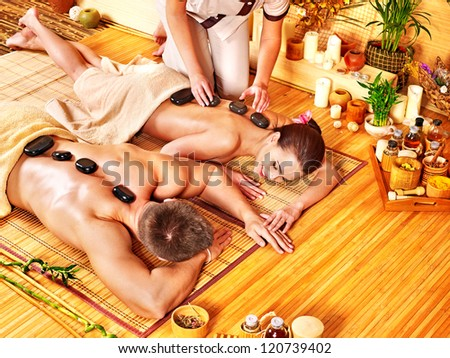 Woman and man getting stone therapy massage in bamboo spa. - stock photo