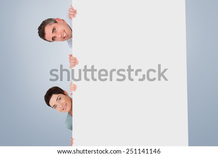 Woman and man hiding behind a blank panel against grey vignette - stock photo