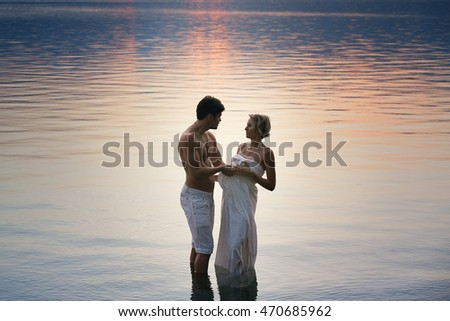 Woman and man hugged in water at sunset. Romance and love