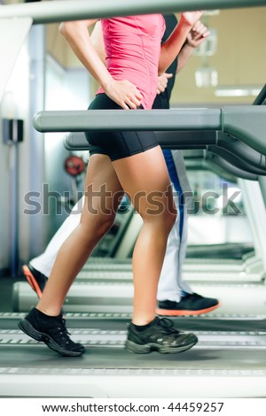 Woman and man in gym - only legs to be seen - exercising running on the treadmill to gain more fitness; motion blur in limbs for dynamic - stock photo