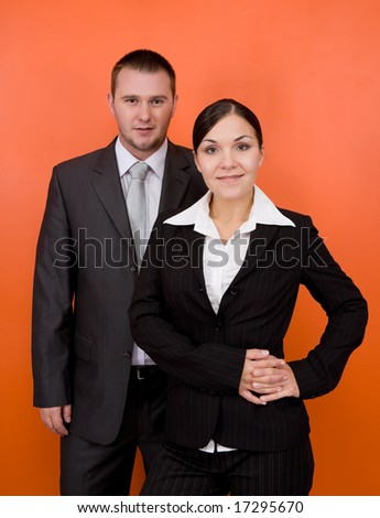 woman and man in team standing on orange background