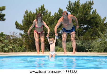 Woman and man omit child in pool - stock photo