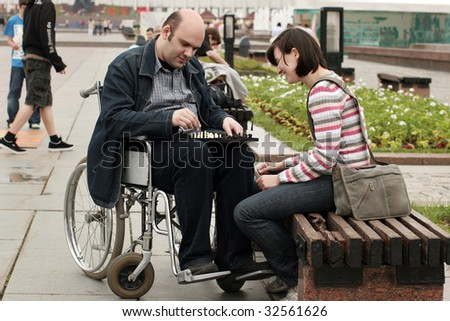 Woman and man on a wheelchair play chess in park - stock photo