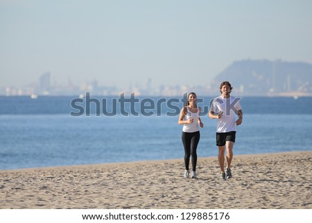 Woman and man running on the beach towards the sea with Barcelona city in the background - stock photo