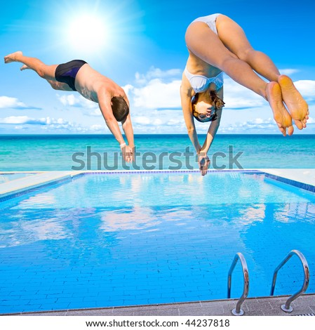 woman and man - simultaneously diving into pool - stock photo