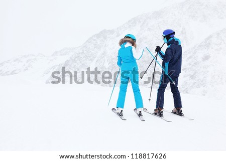 Woman and man skiers in blue suits and helmets prepare for slope at winter in snowy mountains. - stock photo