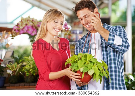Woman and man standing with a green plant (philodendron cordatum) in a nursery shop - stock photo