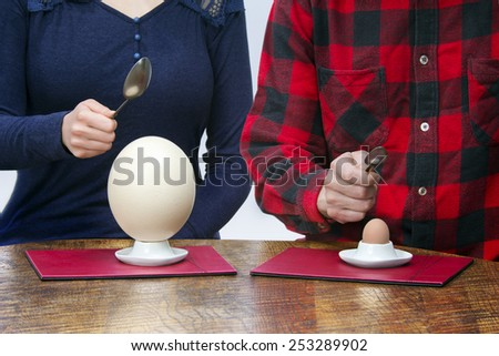 Woman and man with small and big spoons eating hen and ostrich eggs - stock photo