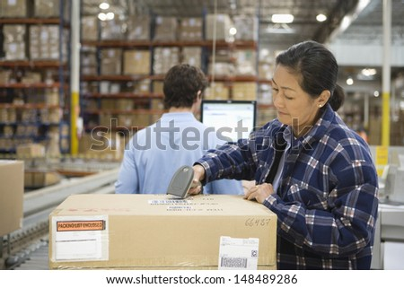 Woman and man working in distribution warehouse - stock photo