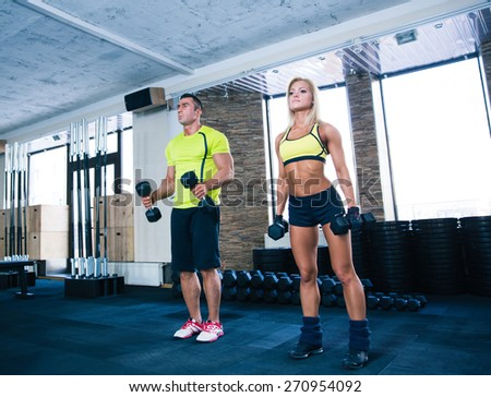 Woman and man working out with dumbbells at gym - stock photo