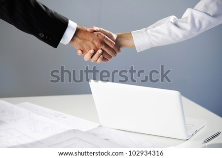 Woman and men shaking hand, laptop on background - stock photo