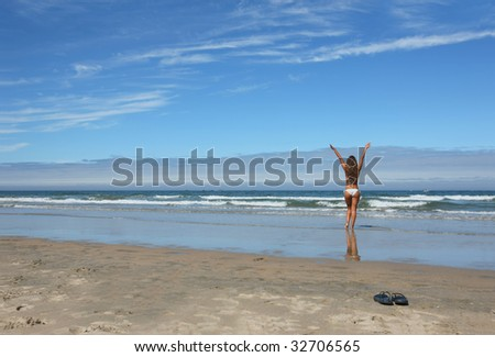 woman and pair of flops in the beach - stock photo
