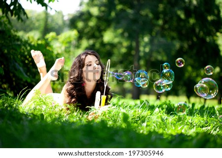 Woman and soap bubbles in park. Beautiful young girl lying on the grass in the field. Smiling trendy stylish woman on nature  - stock photo
